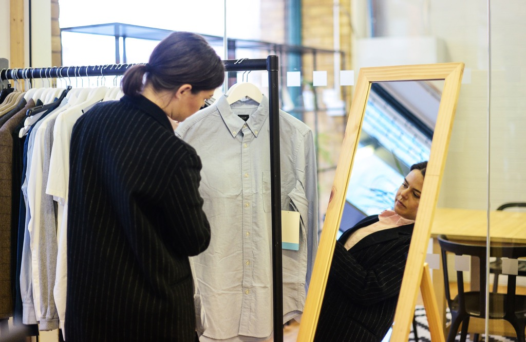 A Stylist chooses a shirt from a rack
